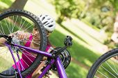 image of mountain chain  - Young woman in helmet trying to fix a chain on mountain bike in the park - JPG