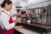 stock photo of jug  - Pretty barista steaming jug of milk at coffee machine in a cafe - JPG