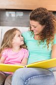 pic of storybook  - Happy mother sitting with her little daughter reading a storybook at home in living room - JPG