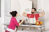 picture of pot-bellied  - Pregnant woman and happy man in the kitchen - JPG