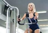 stock photo of execution  - happy cutie athletic girl execute exercise on exercise bicycle and smile in sport - JPG