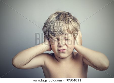 boy with closed ears on a gray background