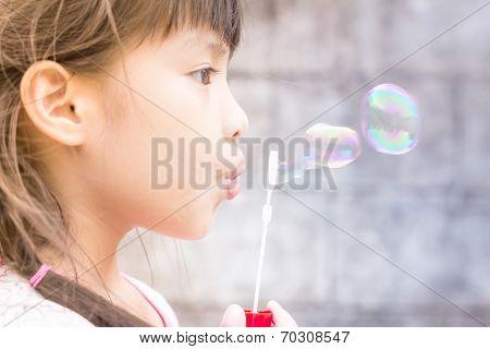 Little Asian Girl Blowing Soap Bubbles