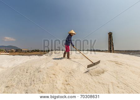 a woman wearning conical hat is raking on the heap of salt at Binh Thuan , Vietnam in daylight.