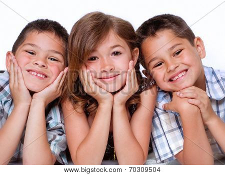 Portrait of three children, two boys and a girl aged between 5 and 8 isolated against white background