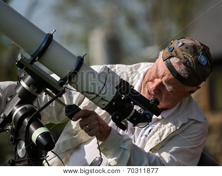 Senior Man Setting Up A Telescope