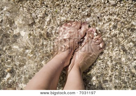 feet of little child in the sea on the beach - holiday