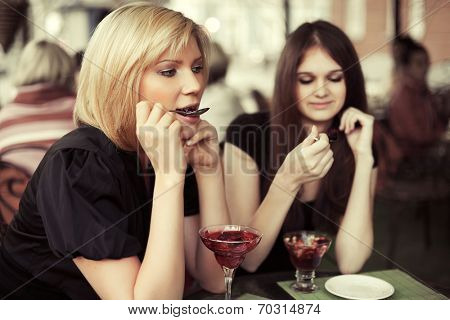 Two young fashion women eating a dessert at sidewalk cafe