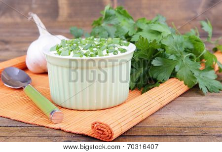 Plastic round bowl of cream with a tuft of parsley and garlic near it on an orange napkin on wooden background