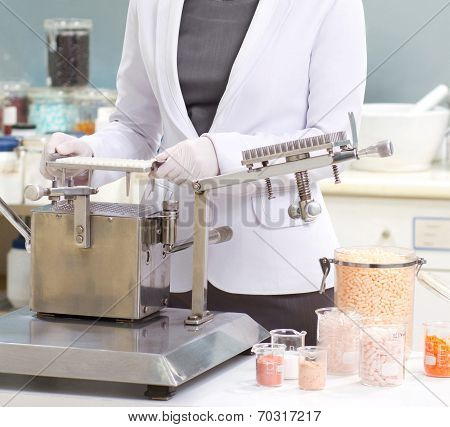 pharmacist preparing medication with packaging capsule machine