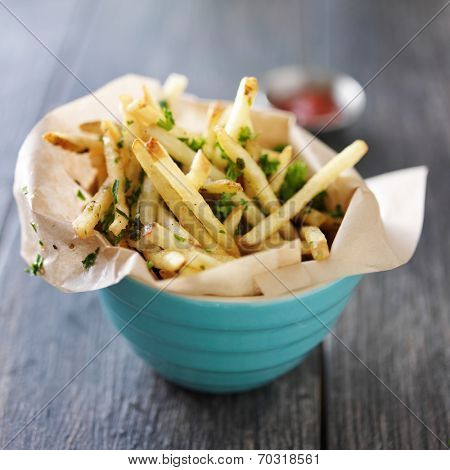 truffle fries standing up in a bowl with wax paper lining