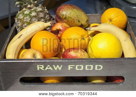 Fresh organic fruit in wooden box ,  RAW FOOD text