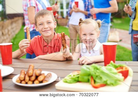 Children eating grilled sausages at family village