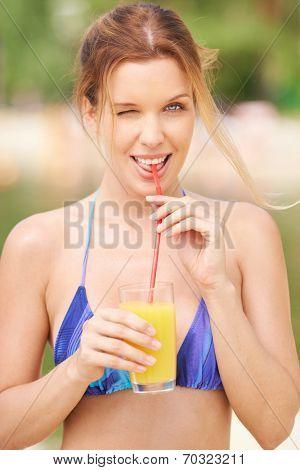Flirty woman drinking juice
