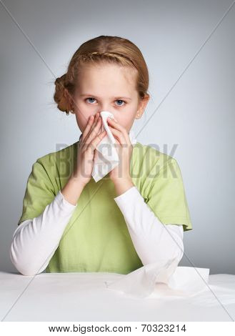 Portrait of an ill girl blowing her nose