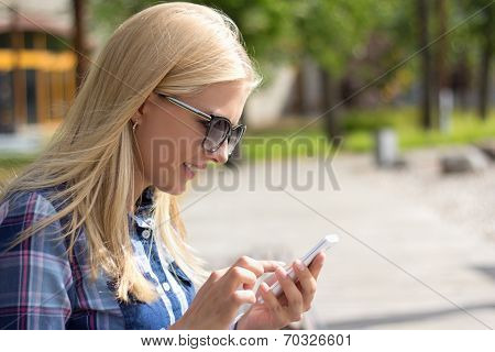Attractive Woman Using Smartphone In Park