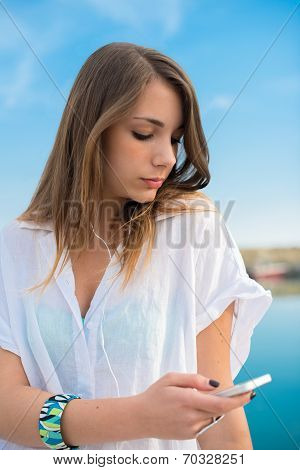 Young Girl Relaxing While Earing Music At The Dock