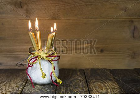 Four Golden Candles -  Traditional Christmas Decoration On A Wooden Background