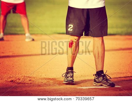 a man's legs on a baseball or softball field with a big scrape toned with a retro vintage instagram filter