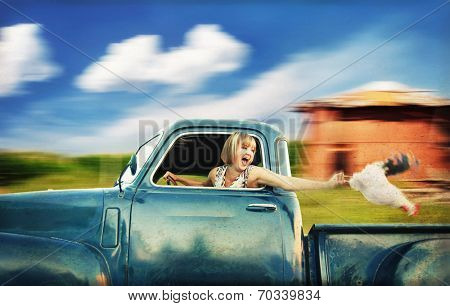 a pretty woman driving a truck past a red barn next to a cornfield