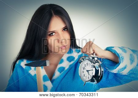 Young Woman Holding a Hammer and an Alarm Clock
