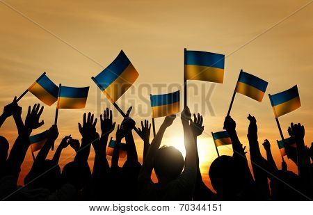Group of People Waving Ukranian Flags in Back Lit