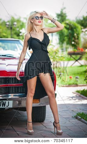 Summer portrait of stylish blonde vintage woman with long legs posing near red retro car