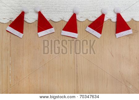 Red Christmas Hats On A Wooden Background For A Greeting Card