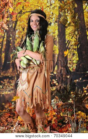 A beautiful Indian teen carrying an armload of corn.  She's in a colorful  fall setting.