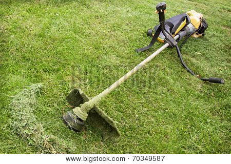 Petrol Trimmer Is On The Sloped Lawn