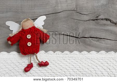 Red Christmas Or Guardian Angel On Grey Wooden Background For A Greeting Card