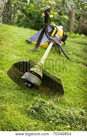 Petrol Trimmer On The Sloped Lawn