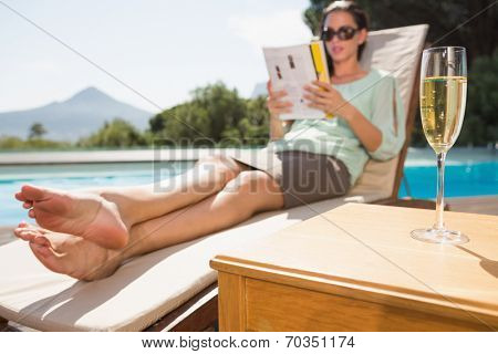 Woman reading book by swimming pool with champagne on table in foreground