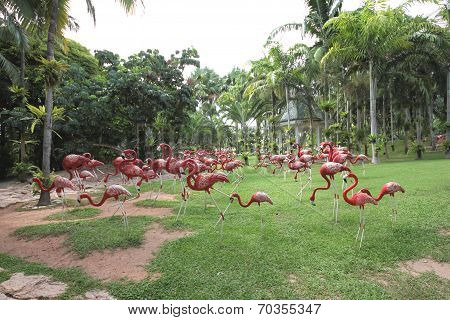 A meadow with pink flamingo and grass and trees and stones in the Nong Nooch tropical botanic garden