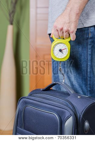 Man checking luggage weight with steelyard balance