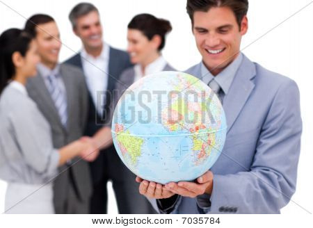 Cheerful Businessman Holding A Globe In Front Of His Team