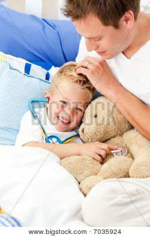 Smiling Father And His Sick Son Playing With A Stethoscope