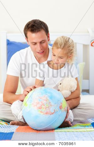 Father And Daugther Looking At A Terrestrial Globe