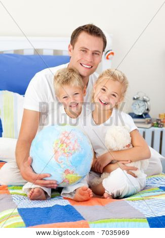 Adorable Siblings And Their Father Looking At A Terrestrial Globe