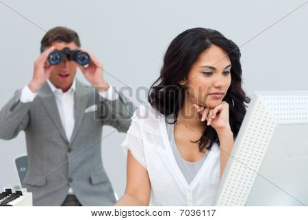 Mature Businessman Looking His Colleague's Computer Through Binoculars