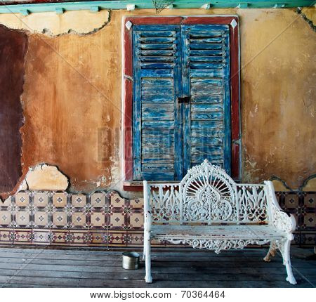 Ornate white wrought iron bench standing on a wooden floor or deck in front of a window with closed weathered blue wooden shutters in a grunge stained dilapidated wall with cracked decorative tiles