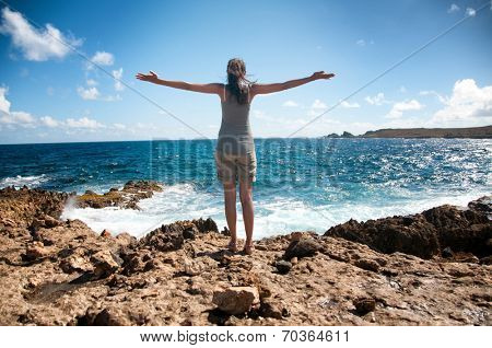 Young woman celebrating the beauty of nature standing on the rocks overlooking the sea with her arms outspread as she embraces the sun and life