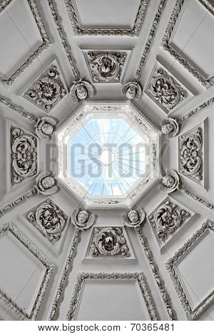 Looking up into a domed roof with a skylight at the top where all the ornate panels with their relief carvings converge with a glimpse of blue sky, architectural background