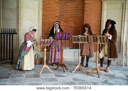 HAMPTON COURT, UK - AUGUST 03, 2014 - Traditional Musicians wearing medieval clothes perform at Hampton Court Palace near London on August 03, 2014