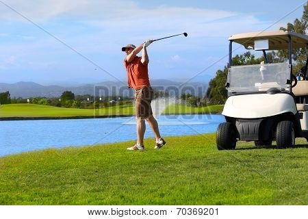 Golfer hitting golf ball next to his cart