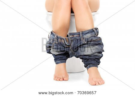 Female seated at a toilet with her pants down isolated on white background
