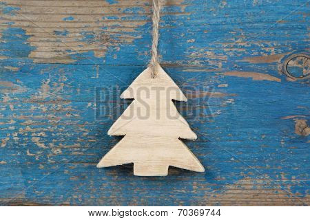 Top View Of Hanging Carved Pine Tree On Wooden Background For Christmas In Blue