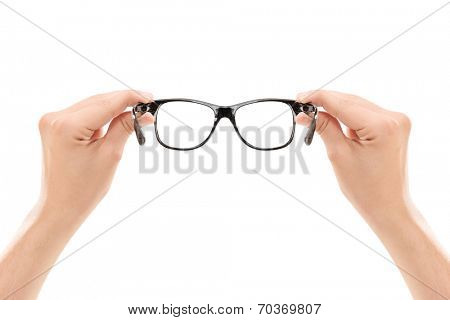Male hands holding a pair of glasses isolated on white background
