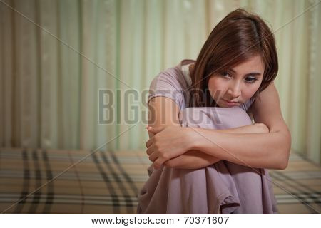 Sad Woman Sitting On The Bed