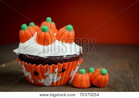 Halloween cupcakes on wood table with vanilla icing and creamy pumpkins on top